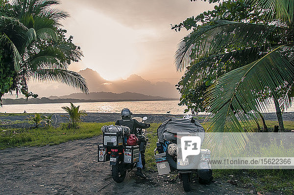 Rear view of man sitting on motorcycle near tropical beach  Puerto Viejo  Limon Province  Costa Rica