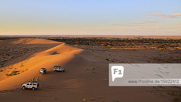 Three vehicles parked in the setting sun atop sand dunes