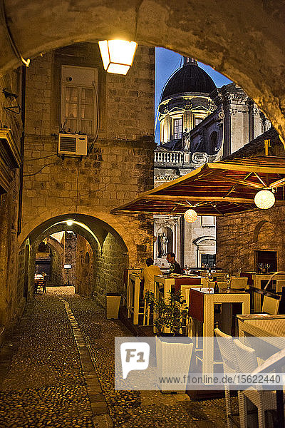 Restaurant tables are lit up at dusk in an alley in Dubrovnik  Croatia.