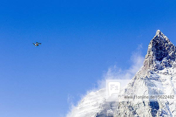 Drone flying against clear sky beside mountain peak