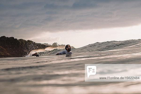 Professional surfer Jonathan Gonzalez paddling back to peak as sun sets  Tenerife  Canary Islands  Spain