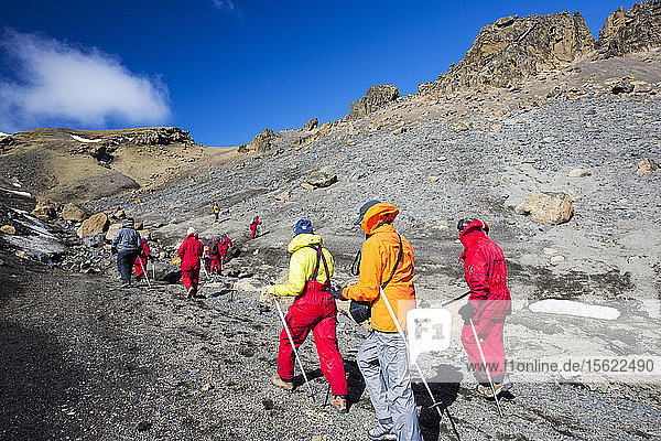 Passengers on an expedition cruise climbing the caldera on Deception Island in the South Shetland Islands off the Antarctic peninsula which is an active volcanic.