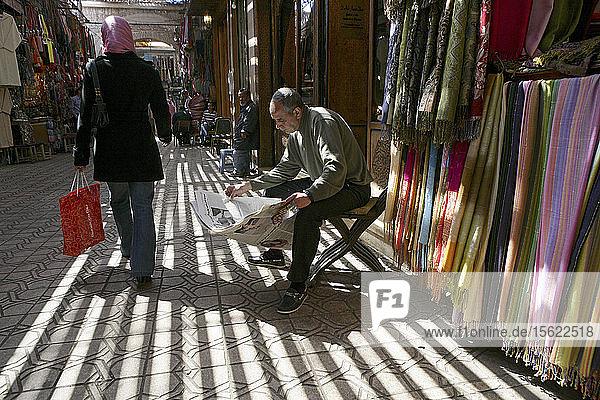 A merchant reads the newspaper in Marrakesh's medina quarter