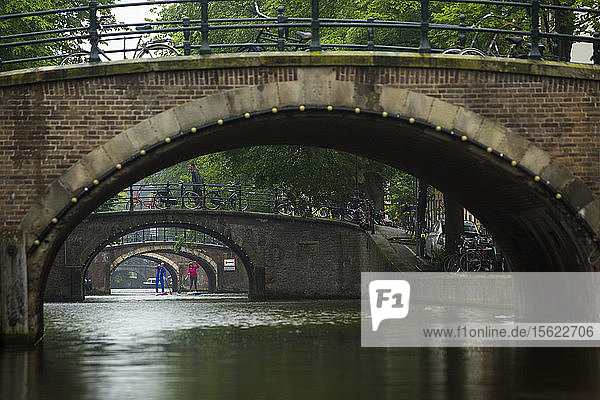 Two peopleï¾ paddle boardingï¾ in city canal under arch bridges  Amsterdam  Amsterdam  Netherlands