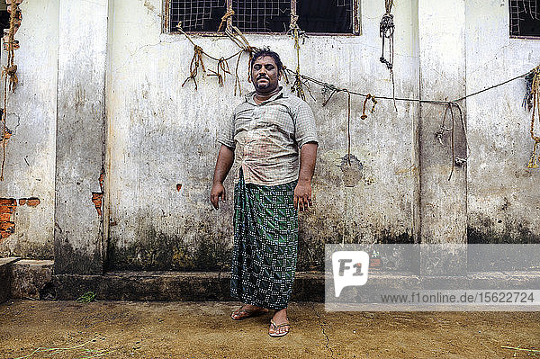 A butcher in front of a butchery  Cochin  Kerala  India.