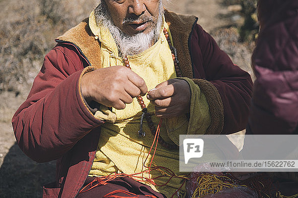 A Buddhist monk ties a prayer knot for a Himalayan trekker.