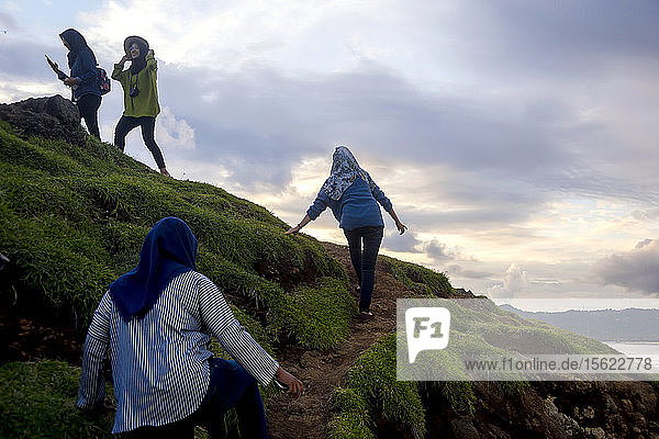 Women traveling on path up hill