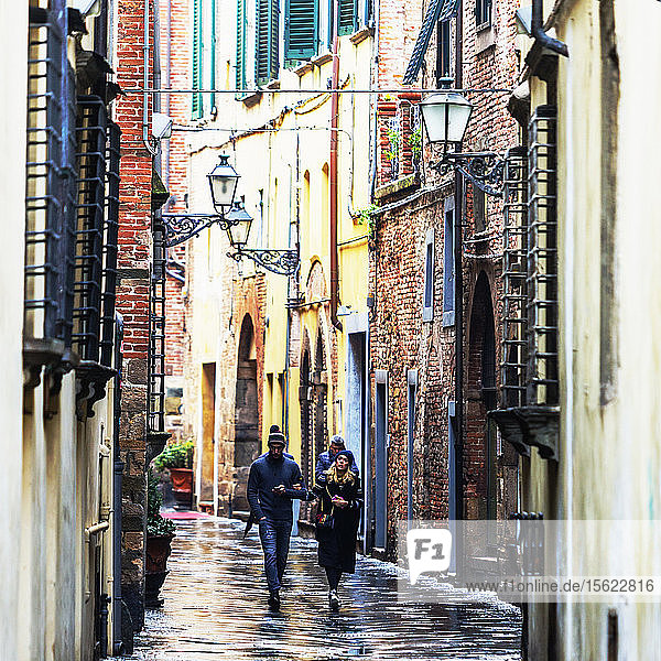 Front view of people walking the wet city streets in Lucca  a city and commune in Tuscany  Central Italy  on the Serchio  a fertile plain near the Tyrrhenian Sea. It is the capital of the Province of Lucca. It is famous for its intact Renaissance-era city walls.