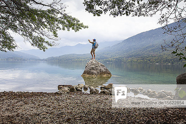 A man is taking a picture whilst standing on a rock at Lake Bohinj in Slovenia. Lake Bohinj with its surroundings is one of the top natural pearls of Slovenia. It lies within Triglav National Park enclosed by the beautiful Julian Alps. Crystal clear water offers bathing between June and September  but the area around the lake draws fans of various sport activities and pristine nature environment throughout the year.