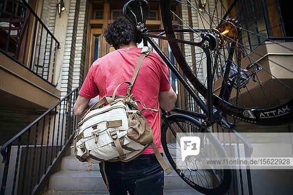 A man carrying his bike up the stairs to his apartment.