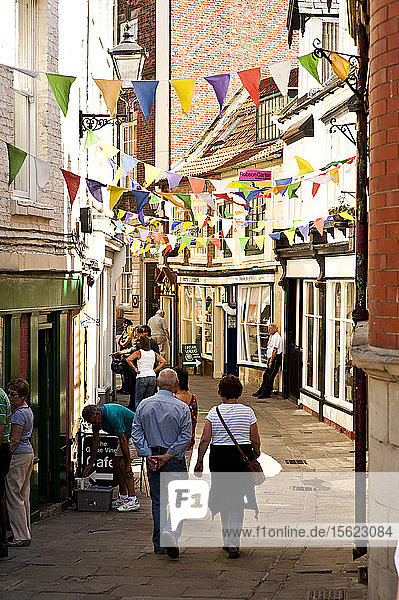 People walk the back streets of Whitby  England on a sunny afternoon.