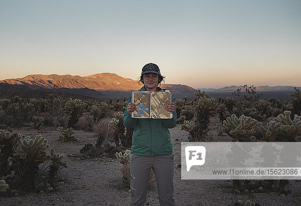 Portrait of woman standing in Chollah Cactus Garden and holding guidebook  California  USA