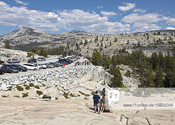 A giant outcrop of nearly bald granite known as Olmsted Point gives Yosemite National Park visitors a chance to explore and appreciate the magnificent Sierra scenery viewable from the Tioga Road. The tip of famous Half Dome is visible mid-right.