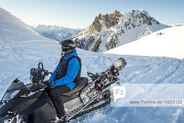 Man sitting on snowmobile in winter  Whistler  British Columbia  Canada