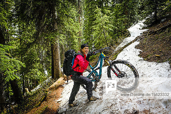 Female mountain biker in forest pushes bike though snow on the Ice Lakes trail  USA