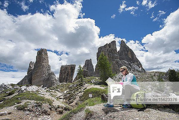 A Woman Reading A Map At Cinque Torri Area In The Dolomites  Italy