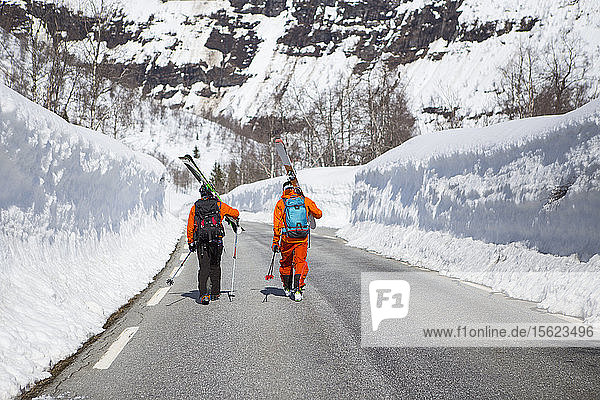 Two Skiers Walking On A Road Between Two High Walls Of Snow Near The Ski Resort At Myrkdalen  Fjord  Norway