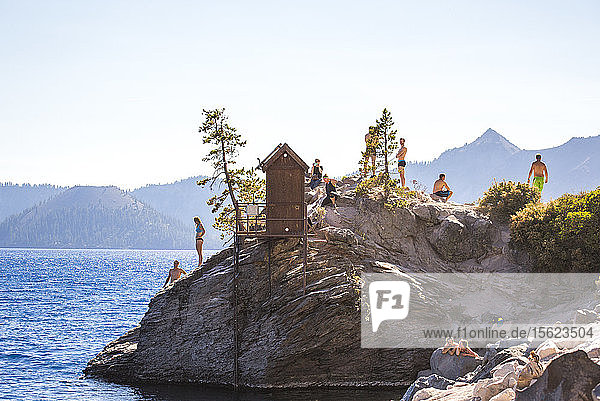 Swimmers wait on a rock outcrop surrounded by a big blue lake on sunny summer day  Crater Lake  Oregon  USA