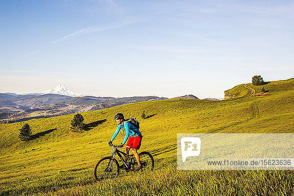 A young woman rides a mountain bike on single-track trail through green grass in early morning sunlight with volcano in distance.