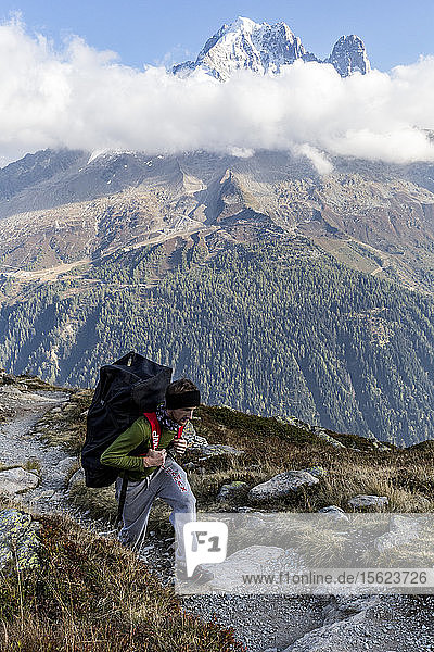 Man hiking in mountains with paddle board on back  Chamonix-Mont-Blanc  Haute-Savoie  France