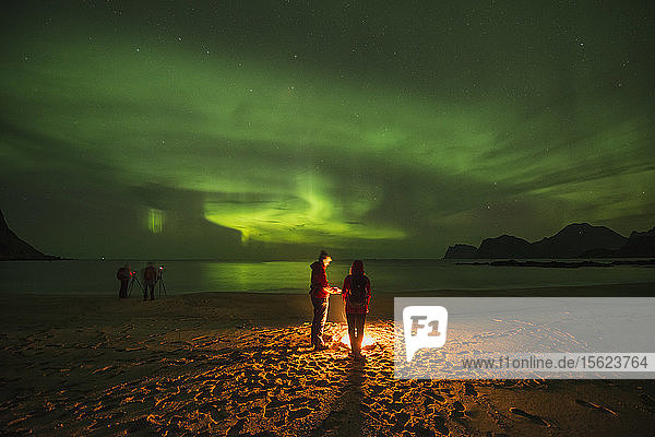 Tranquil scene with people around campfire on beach under aurora�borealis�at night  Flakstadoya  Lofoten Islands  Norway