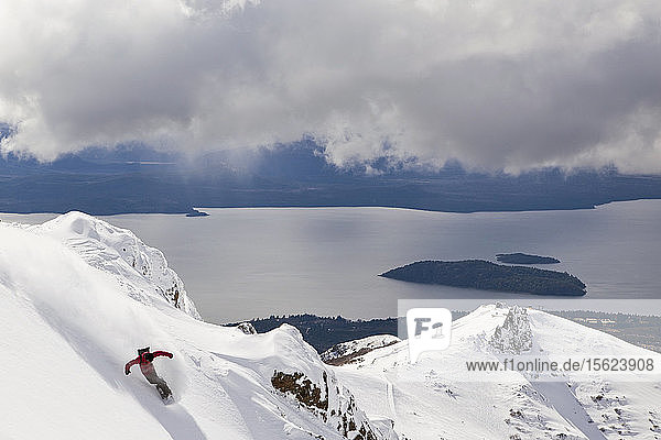 A Snowboarder Makes A Powder Turn And Sprays Snow Into The Air