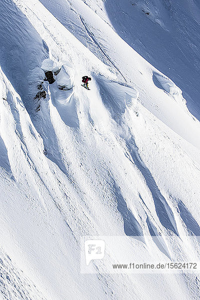 Professional Snowboarder Helen Schettini  catches air and grabs her board on a sunny day while snowboarding in Haines  Alaska.