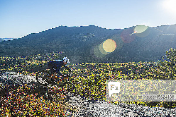 Mountain Biker Riding On The Bare Granite Slabs Of The Whitehorse Ledge  New Hampshire