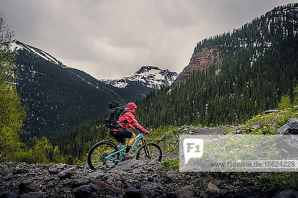 Woman mountain biker in scenic landscape rides the Ice lakes trail in the rain  USA
