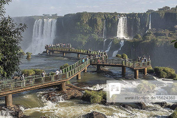 Large group of tourists on bridge enjoying beautiful landscape ofï¾ Iguazuï¾ Falls  Parana  Brazil
