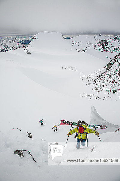Skiers boot pack with gear on their back up a steep slope to a notch in the Coast Mountains during the Spearhead Traverse in Whistler  British Columbia  Canada.