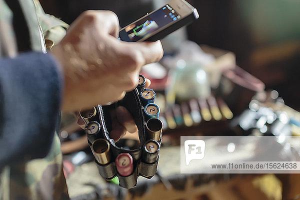 Young man with smart phone and shotgun ammunition  Tikhvin  Saint Petersburg  Russia