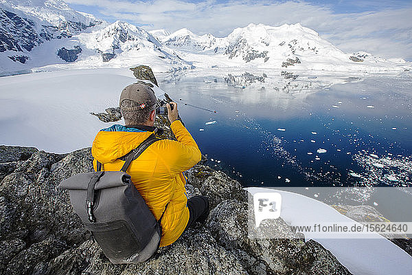 A passenger from an Antarctic cruise ship amongst stunning coastal scenery beneath Mount Walker in Paradise Bay off Graham Land on the Antarctic peninsula. The peninsula is one of the most rapidly warming places on the planet.