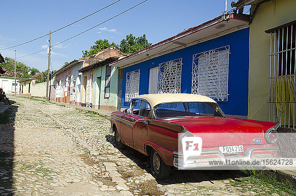 A car sits parked on the cobblestone streets of Trinidad  Cuba.