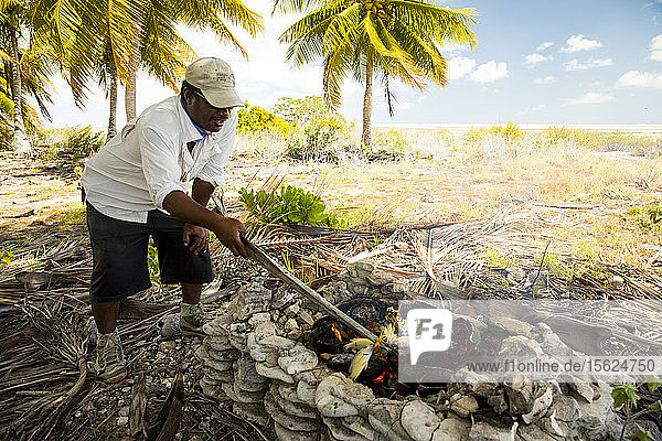 Man cooking fish over campfire on Christmas Island  Kiribati