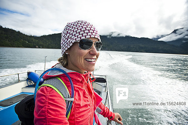 A girl in adventure gear riding on the back of a boat near Homer  Alaska.