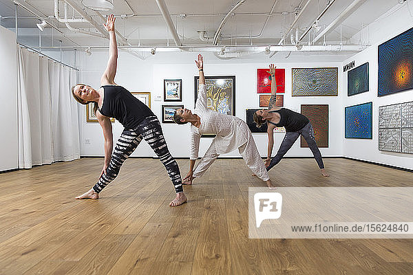 Three Women In Triangle Pose Yoga Asana In An Art Gallery