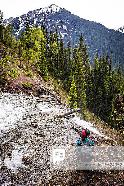 Woman hiker in scenic landscape stopping to take in the sights on the Ice Lakes trail  USA