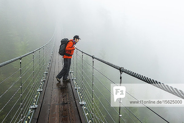 A man looks over a suspension bridge on a rainy fall day in Squamish  British Columbia.