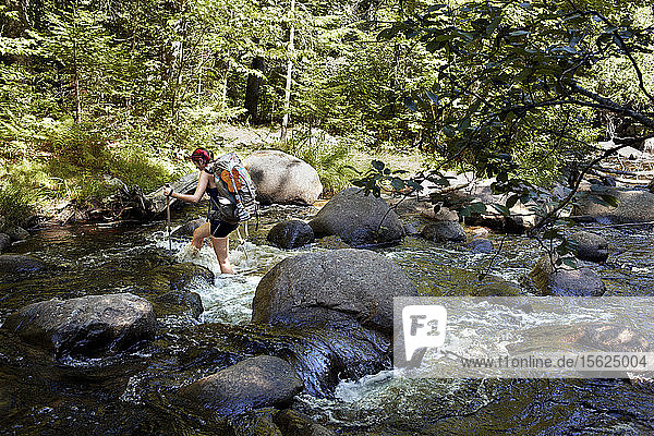 A female hiker crossing a river in Maine's Baxter state park.��