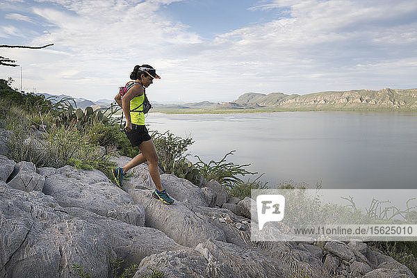 Middle adult woman running down rocky trail in area of Presa El Zarco  Durango  Mexico