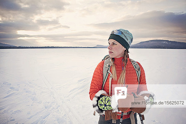 A female nordic skier poses for a portrait on frozen Flagstaff Lake  Maine.