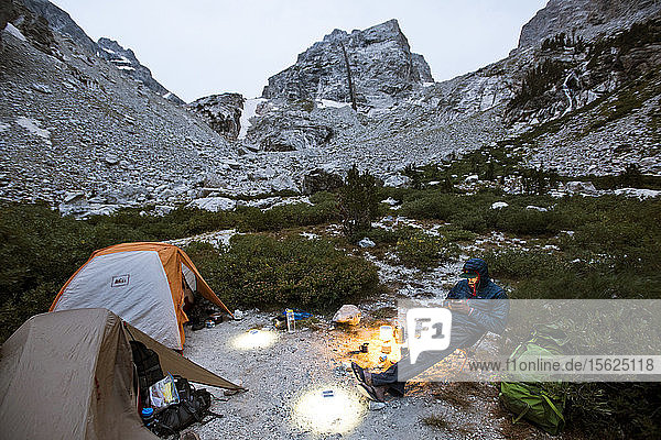A Hiker Using His Phone While Relaxing At Camp In Grand Teton National Park