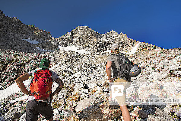 Two Male Hikers On Rocky Landscape Of Grand Teton National Park