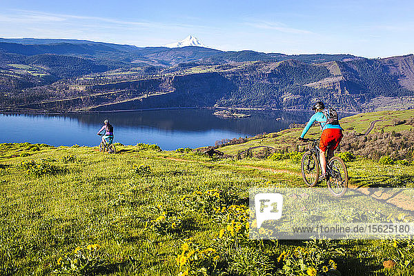 Two young women ride mountain bikes on single-track trail through a meadow with volcano in distance.