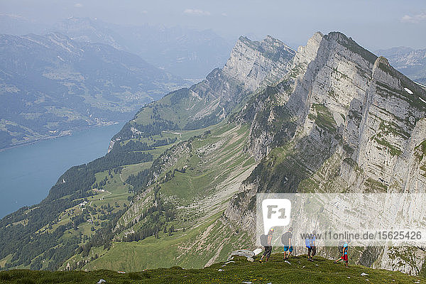 A group of base jumpers hiking in the Alps above Lake Wallen to find their next flight sight. Toggenburg  Switzerland