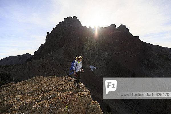 Female Hiker hiking along a rock formation in front of 3 fingered jack.