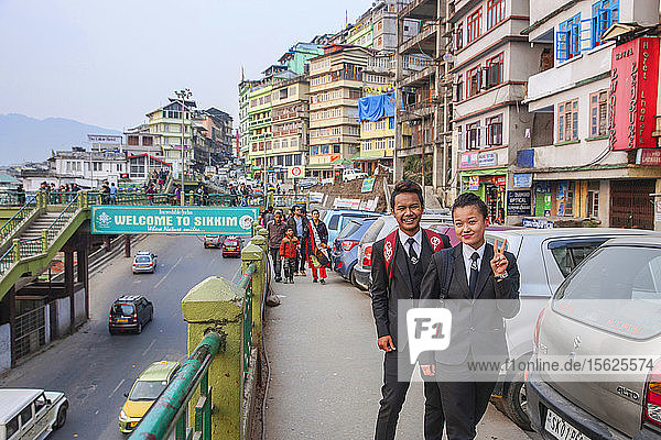A young couple pose for the camera in front of a busy Sikkim street scene. Gangtok  Sikkim  India.