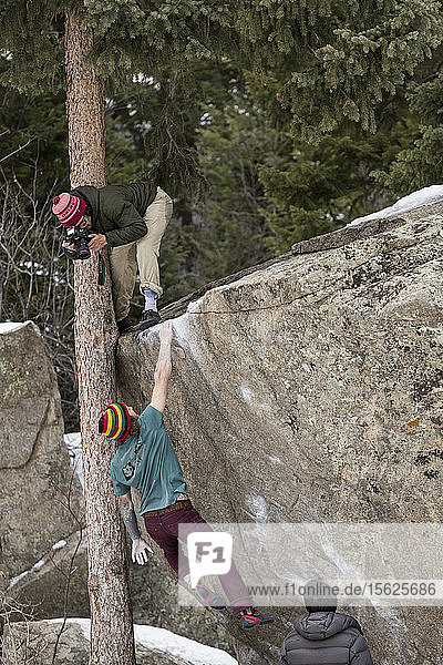 A male climber dynos to the lip of a boulder while a photographer shoots from above