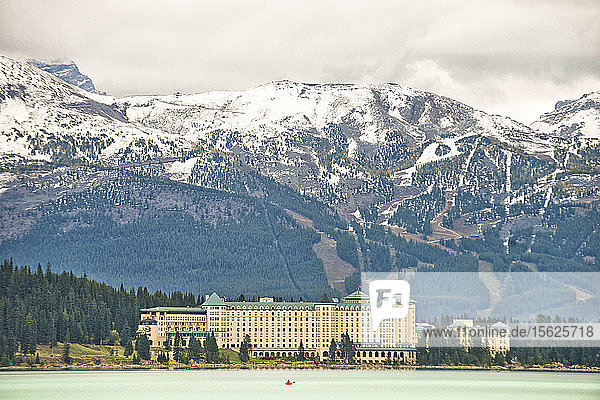 A man in a canoe is seen on Lake Louise in front of the Fairmont Chateau and Lake Louise Ski Resort.